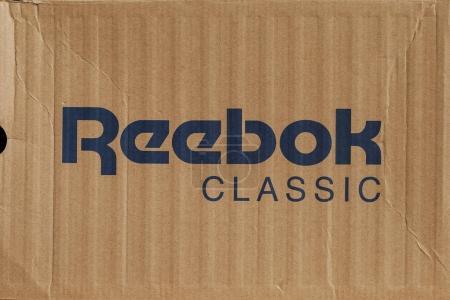 KIEV, UKRAINE-JULY 19,2017: blue Reebok sign with light brown background, Reebok International Ltd. - Sports shoe and sewing company.