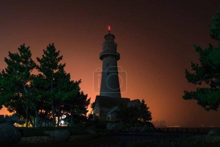 Photo for Lighthouse silhouette. Night marine embankment of Weihai - Royalty Free Image