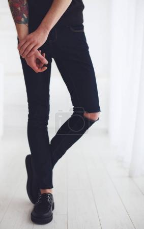 Photo pour Jambes minces d'un jeune homme portant déchiré jeans et des chaussures en cuir - image libre de droit