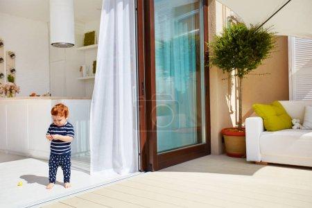 Photo pour Un bébé tout-petit marchant sur la cuisine ouverte avec patio sur le toit et portes coulissantes - image libre de droit