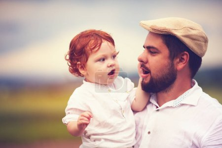 Photo for Portrait of father and cute redhead son in the countryside - Royalty Free Image