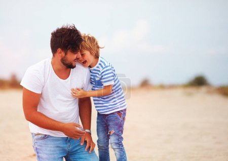 Photo for Candid image of father and son laughing, having fun together - Royalty Free Image