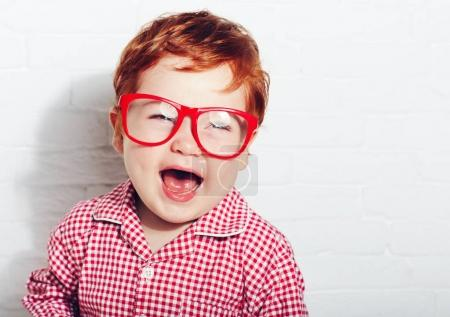 Foto de Retrato de chico lindo de niño ríe en los vidrios - Imagen libre de derechos