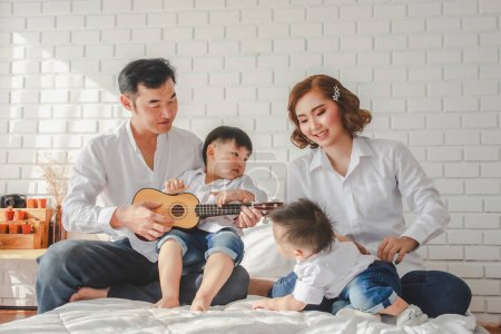 Photo for Asian Japanese Family father mother son wearing white shirt hold camera, guitar aculele - Royalty Free Image