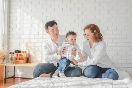 Photo for Asian Japanese Family father mother son wearing white shirt carrying child posing for photo on bedroom in white room.To keep memories moment cuteness of son in childhood lifestyle happy - Royalty Free Image