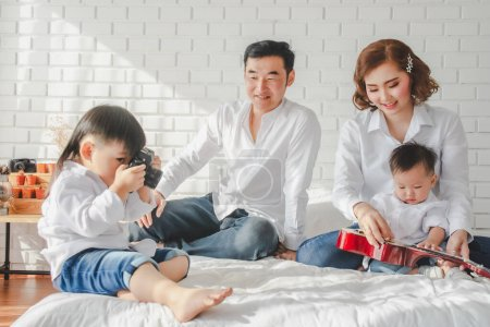 Photo for Asian Japanese Family father mother son wearing white shirt hold camera, guitar aculele posing photo on white bedroom in white room house.To keep memories moment cuteness of son - Royalty Free Image