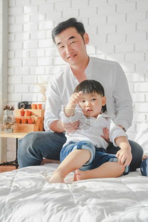 Photo for Asian Japanese Family father son wearing white shirt carrying child posing for photo on bedroom in white room.To keep memories moment cuteness of son in childhood lifestyle happy - Royalty Free Image