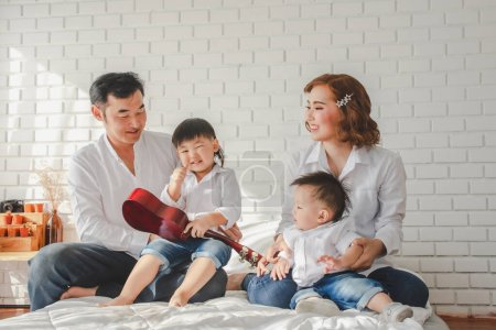 Photo for Asian Japanese Family father mother son wearing white shirt hold guitar aculele posing photo on white bedroom in white room house.To keep memories moment cuteness of son - Royalty Free Image