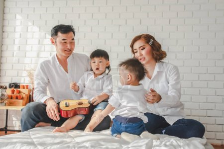 Photo for Asian Japanese Family father mother son wearing white shirt hold guitar aculele posing photo on bedroom in white room.To keep memories moment cuteness of son in childhood lifestyle happyAsian Japanese Family father mother son wearing white shirt hold - Royalty Free Image