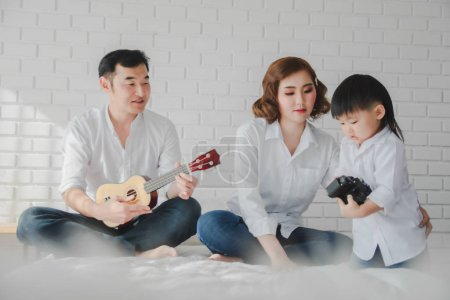 Photo pour Asiatique Japonais Famille père mère fils portant chemise blanche tenir aculele guitare posant photo sur chambre à coucher en chambre blanche.Pour garder des souvenirs moment de douceur du fils dans le mode de vie de l'enfance heureuxAsiatique Japonais Famille père mère fils portant chemise blanche tenir - image libre de droit