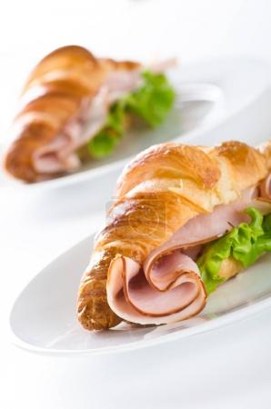 delicious fresh croissant with ham and lettuce