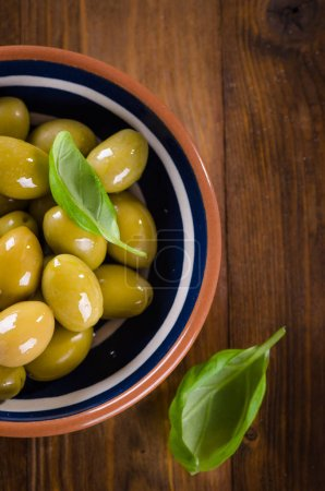 Green olives in ceramic bowl on wooden background