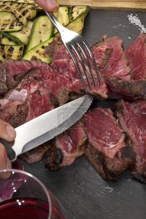Photo for Man eating grilled T-bone sliced beef steak and vegetables - Royalty Free Image