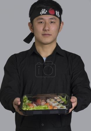 Young asian chef holding plastic box with sushi