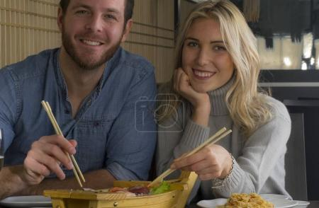Caucasian young couple eat from sushi wood boat at restaurant