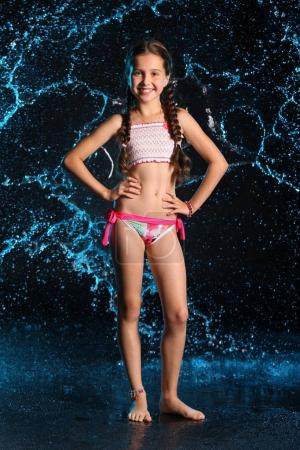 Photo for Happy young teenage girl in a swimsuit stands barefoot in splashing water. Pretty child with dark hair and beautiful face adorably smiles. Slender preteen in a bikini. - Royalty Free Image