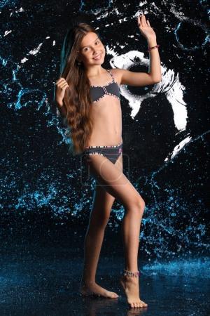 attraktive, glückliche junge Teenagerin posiert in einem dunklen Bikini. das Kind mit den langen schicken Haaren und dem schönen schlanken Körper lächelt charmant. Schöne Pre-Teen Tänze barfuß im Badeanzug.