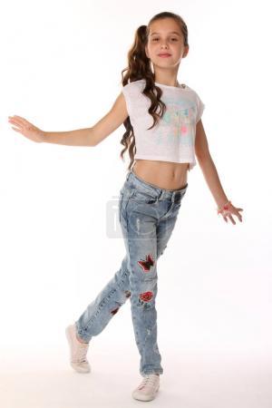 Porträt eines glücklichen, schlanken, fröhlichen Teenagermädchens mit vollem Körper. das Kind posiert elegant und lächelt. junge Fashionista in blauen Jeans und mit nacktem Bauch.