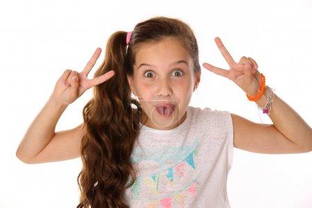 Nahaufnahme Porträt eines fröhlichen, ziemlich fröhlichen Teenagers. das Kind in lustigen Posen macht ein komisches Gesicht und zeigt seine Zunge.