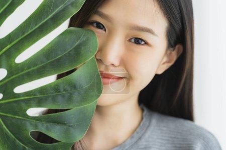 Photo pour Belle chemise blanche femme asiatique profiter de jouer avec vert feuille légumes vegan ides concept sur blanc lit vacances style de vie - image libre de droit