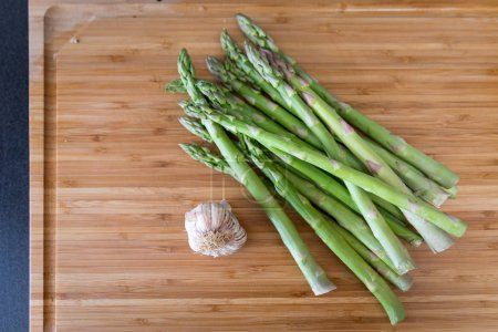 Green organic asparagus with garlic on wooden cutting board background