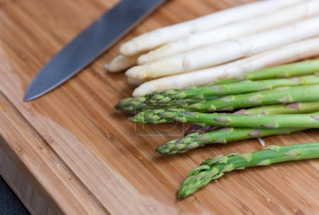 Green and white asparagus with knife on wooden cutting board, food preparation
