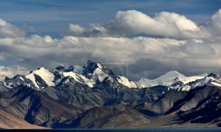 Powerful mountain peaks with snow-capped peaks, clouds of stripes lie on tops of the mountain, the Himalayas.