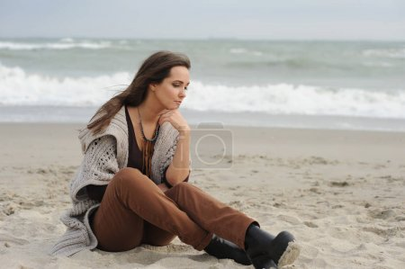 Sad woman sitting on a sea beach