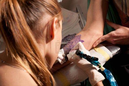 Photo pour Jeune femme mignonne tatoueuse maîtresse fait le tatouage à portée de la main sur un bleu violacé ressemblant à un tatouage futur, sous la lampe, sans visage - image libre de droit