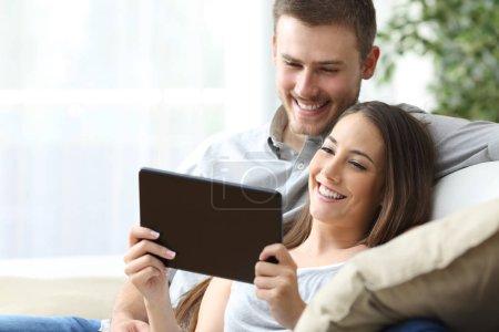 Photo pour Couple occasionnel, je regarde le contenu des médias en ligne dans un comprimé, assise sur un canapé dans le salon à la maison - image libre de droit