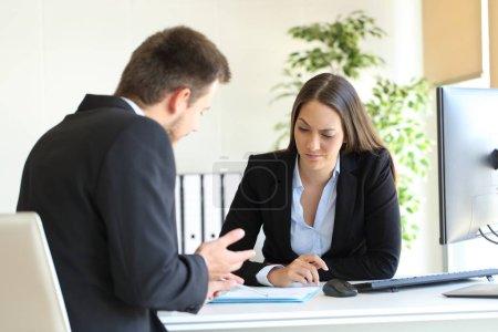 Photo pour Mauvais homme d'affaires essayant de convaincre un client suspect lors d'une négociation difficile dans un bureau au bureau - image libre de droit