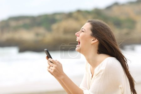 Side view of a exaggerated girl using a smart phon...
