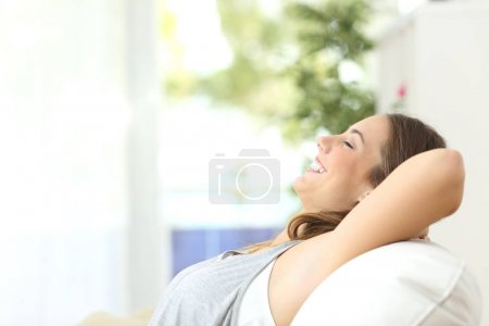 Photo pour Portrait de vue de côté d'une personne détendue, riant assis sur un canapé dans le salon à la maison avec une fenêtre et un fond vert - image libre de droit