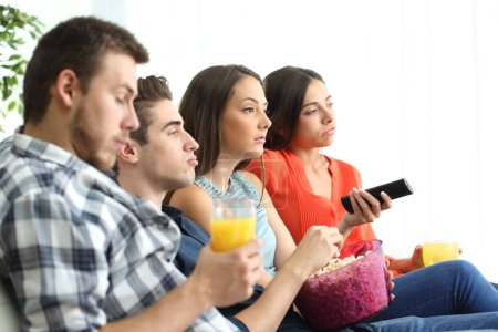 Bored group of friends watching tv at home