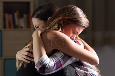 Photo pour Vue latérale de deux amis tristes embrassant dans une chambre à coucher dans un intérieur de maison avec une lumière sombre en arrière-plan - image libre de droit