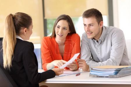 Photo pour Deux clients heureux résolvent des doutes sur un contrat avec la vendeuse au bureau - image libre de droit