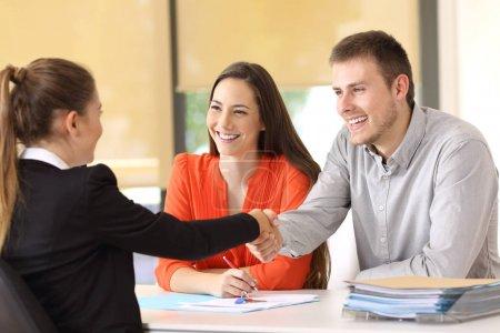 Photo pour Couple de clients heureux poignée de main avec le travailleur après un accord au bureau - image libre de droit