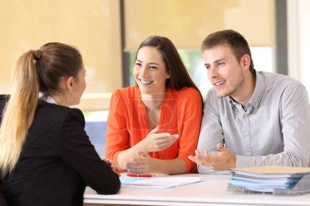 Photo pour Deux clients heureux en conversation avec un employé de bureau - image libre de droit