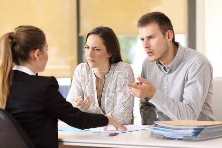 Photo pour Couple en colère réclamant une femme d'affaires au bureau - image libre de droit