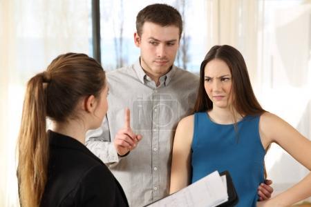 Photo pour Mauvais agent immobilier à mécontentement des clients dans un intérieur de maison - image libre de droit