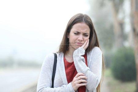 Photo pour Vue de face portrait d'une femme souffrant de maux de dents une journée brumeuse - image libre de droit