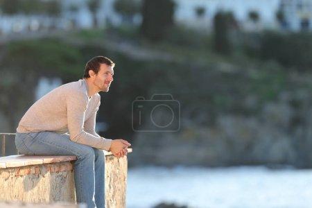 Un hombre serio y pensativo contemplando las vistas de la playa