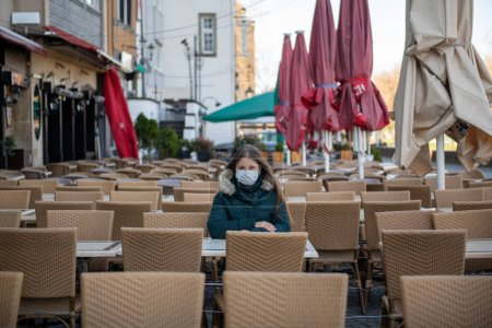 Photo for Serious young woman with protective face mask sitting outdoors at the empty cafe terrace  during the coronavirus outbreak in Cologne, Germany - Royalty Free Image