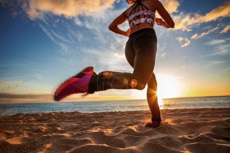 Photo pour Mode de vie sain sport femme courir sur la plage de sable coucher de soleil bord de mer - image libre de droit