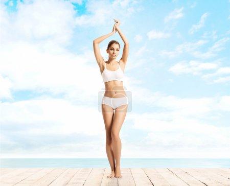 Photo pour Jeune ajustement belle femme en sous-vêtements blancs sur fond bleu ciel - image libre de droit