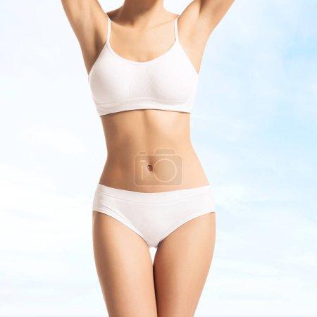 Photo pour Corps mince femme en maillot de bain blanc sur fond bleu clair - image libre de droit
