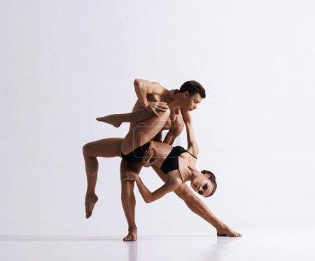 Photo pour Danseurs de ballet dans la performance artistique. Homme et femme sportifs et gracieux dansant - image libre de droit