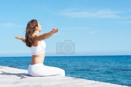 Woman in white dress on wooden pier