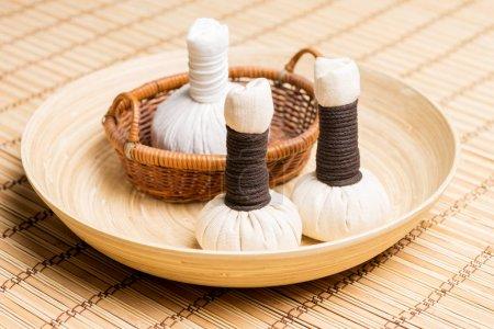 Massage bundles on plate on bamboo mat
