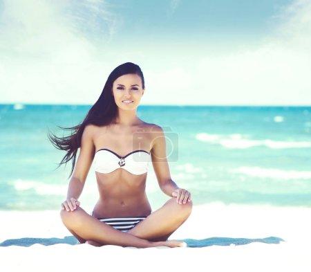 Beautiful woman meditating on summer beach